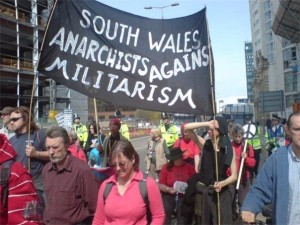 A march, featuring a banner reading 'South Wales Anarchists Against Militarism'
